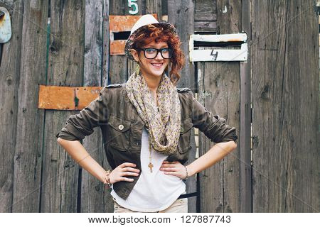 Attractive young hipster with hands on her hips. Trendy youth outfit - reading eyeglasses hat and scarf