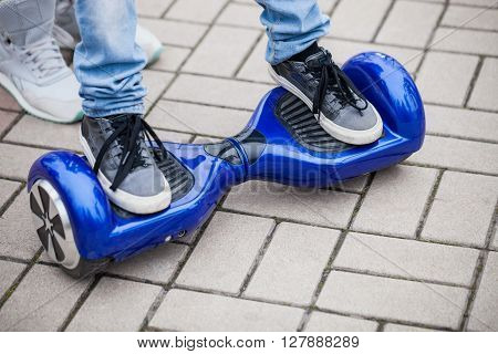 Kid standing on a modern blue electric mini segway or hover board scooterin outdoors. Popular new city transport that is easy and fun to ride and makes no air pollution to the atmosphere