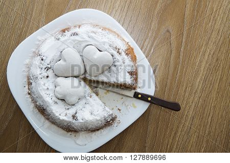 cake with powdered sugar and biscuits in the shape of hearts