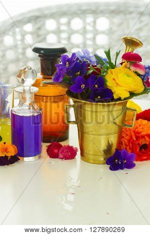 Flowers, mortar and bottles of potions on white table, herbal medicine