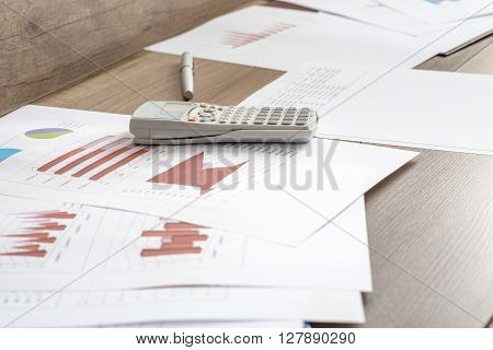 Paperwork with statistical data graphs and charts lying on a wooden office desk together with a pen and calculator.