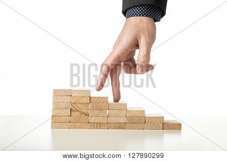 Male hand in business suit walking its fingers up a staircase made of wooden pegs over white background.