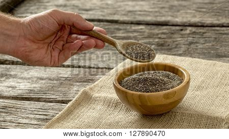 Male hand holding wooden spoon full of nutritional Chia seeds over a wooden bowl of chia seeds sitting on linen cloth.