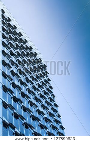 New modern high-rise steel and glass office building with large windows and open air conditioning ventilation system. Toned and filtered stock photo.