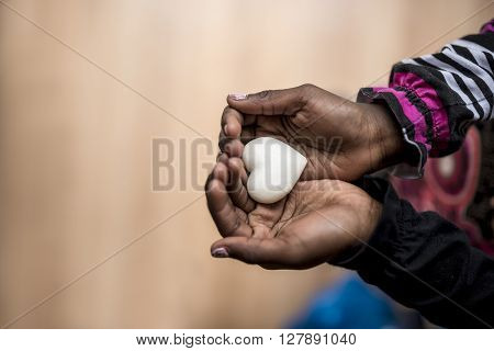 Closeup of African-American girl holding a marble made heart shape in her hands with copy space on the left side of the image.