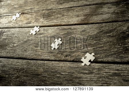 Four blank puzzle pieces lying in a row on a textured rustic wooden desk.