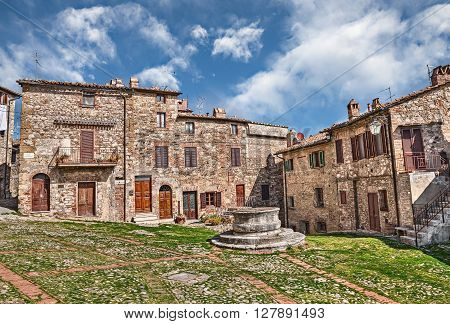 picturesque square with an ancient water well and cobblestone pavement in the italian old town Castiglione d'Orcia, Siena, Tuscany, Italy