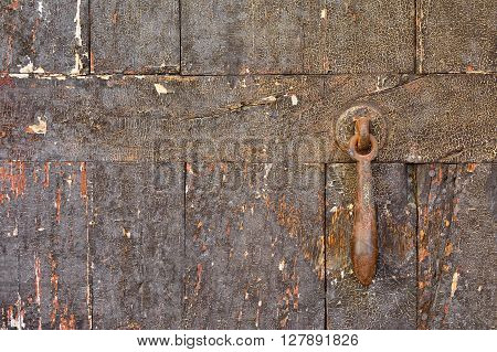 Close-up of worn out shabby wooden door with rusty metal doorbell