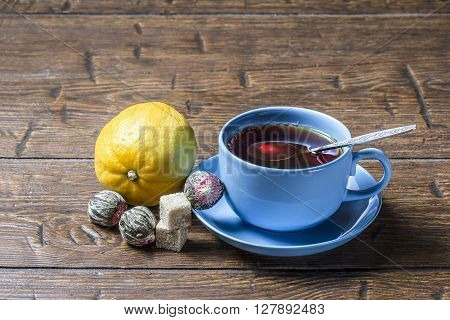 Cup of tea with spoon and lemon on vintage table
