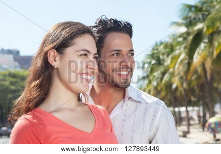 Modern couple in the city looking sideways with modern buildings in the background