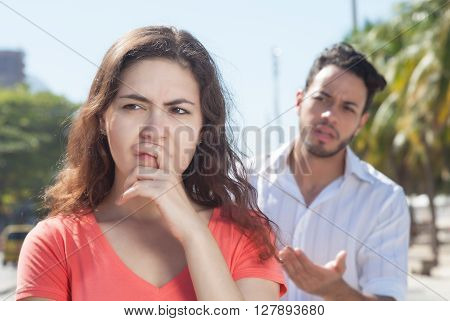 Modern couple with relationship problems in the city with modern buildings in the background