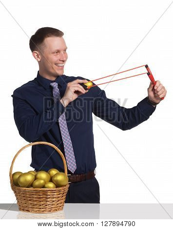Young man shoots the golden egg from his slingshot. In front of him is basket with golden eggs on the table. Concept of investments.