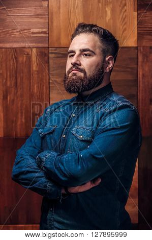 Portrait of Brutal bearded man thinking on a wooden texture in barbershop. Side view of handsome young bearded man keeping arms crossed.