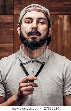 Portrait of bearded hipster with straight edge razor on a wooden texture in barbershop. The guy in the cap holds razor letter V