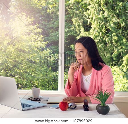 Mature woman wearing pink bathrobe working from home in front of large window with bright daylight and trees in background. Light haze effect applied to image.