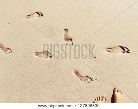 Feet and steps marks on sunny sand beach by sea, summer travel photo,  close up footprints in sand, yellow sand with step marks, vacation by sea, summer holiday, girl on holiday, Bali, Indonesia