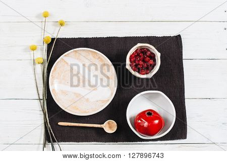 Pottery ceramics set with red decorative pomegranate. Dried fruits in clay bowl top view over white wood table. Beige crockery on white wooden background flat lay.