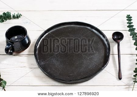 Top view empty black dishes and cutlery on rustic wooden table. Ceramic black plate, cup and spoon on white wooden background. Flat lay of handmade black ceramics on white wooden table.