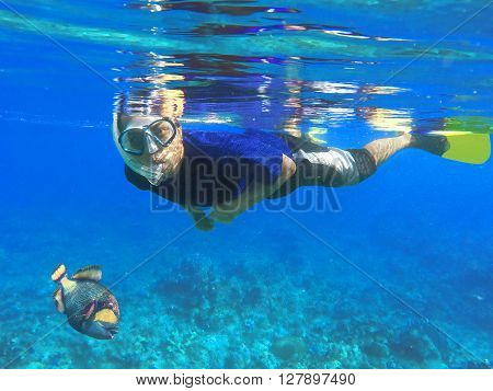 Asian snorkel and big fish under blue water during snorkeling lesson near coral reef, snorkeling with triggerfish, indonesian snorkel in mask, diving to coral reef, Nusa Penida, Bali, Indonesia