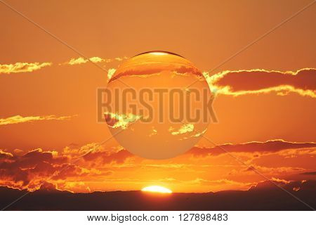 At the sunset floats a transparent sphere in the sky.