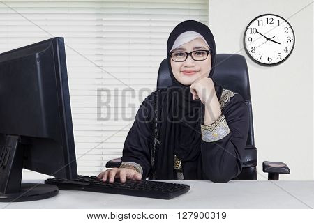 Portrait of Arabian businesswoman sitting in the office while wearing headscarf and looks confident with computer on desk