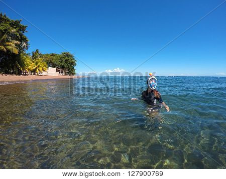 Beautiful woman in the snorkeling mask in the blue sea near tropical beach, snorkel woman in blue mask, tropical sea snorkeling, summer vacation activity, girl swimming in seashore, Philippines