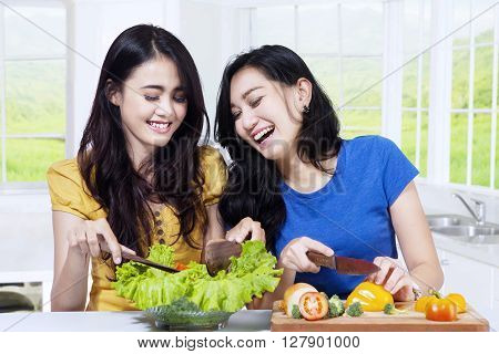 Two healthy Asian women cooking vegetables salad in the kitchen at home