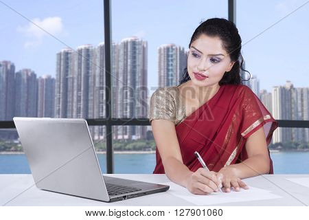 Picture of Indian young businesswoman working in the office while wearing sari clothes and using laptop