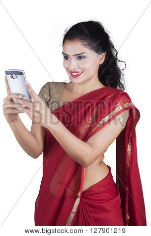Picture of a pretty Indian young woman wearing sari clothes while using mobile phone in the studio