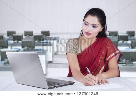 Indian young businesswoman working with laptop computer in the office while wearing sari clothes