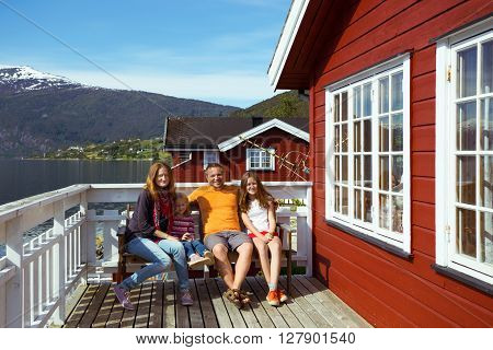 happy family sitting near rorbu. beautiful Norwegian landscape at the fjord and mountains norway