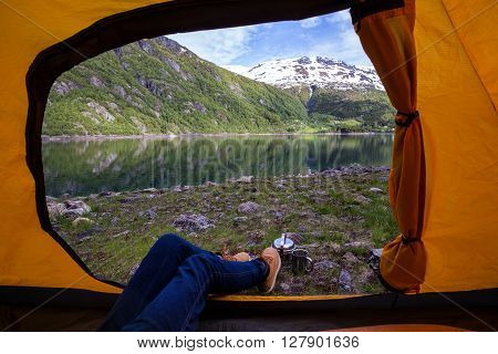 girl hiker in a tent and view of tent on the mountain norway