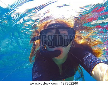 Beautiful woman under water before dive to coral reef, snorkel woman snorkeling in black mask,woman face in mask, tropical sea snorkeling, summer vacation activity, girl swimming, young girl in sea