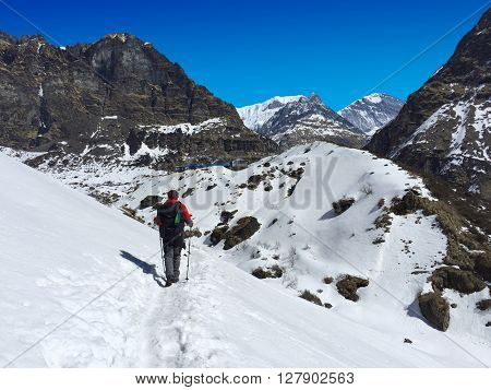 Man trekking in Himalayas, trekker on path through snow mountains, sharp peaks mountains and trekker, active sport on vacation, trekking backpacker in Annapurna, trek to Annapurna base camp, Nepal