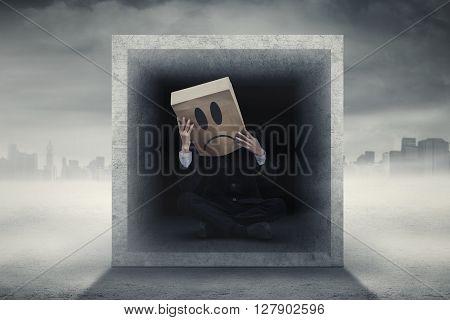 Worried businessman with cardboard head sitting in dark screen with city background