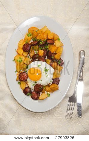 spanish meal with sliced chorizo roasted potato fried egg and parsley on a plate