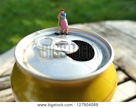 Miniature Cleaning Lady Leaning On Broomstick On Top Of Soda Can With Blurred Background. Business C