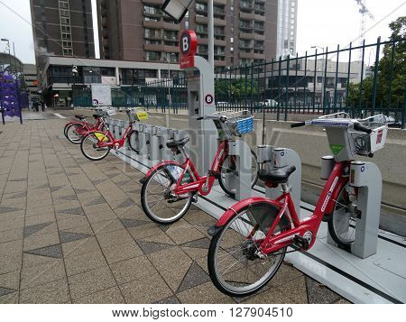 DENVER COLORADO - JULY 7: Row of red bicycles at Bike Share station on a rainy day in Denver Colorado. July 7 2015. Denver Bikeshare features 87 stations and 700 bikes throughout ten central Denver neighborhoods.
