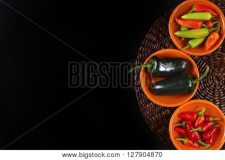 Mexican hot chili peppers colorful mix jalapeno on orange bowls and black background