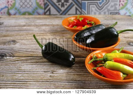 Mexican hot chili peppers colorful mix jalapeno on orange bowls and wooden background