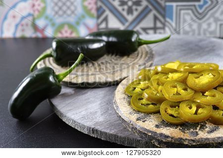 Green fresh and delicious sliced pickled jalapenos on stone with wooden background