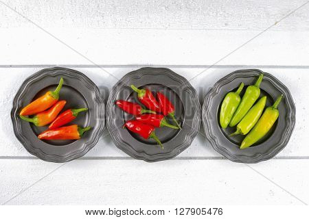 Mexican red green orange hot chili peppers colorful mix jalapeno on metal bowls