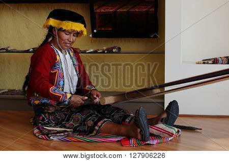 20 November 2010  - Lima, Peru. Peruvian indigenous woman of the middle age is weaving a carpet.  She is wearing peruvian  ethnic tradictional costume.