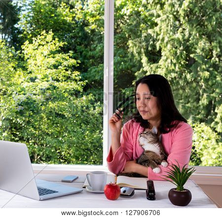 Mature woman wearing pink bathrobe holding her family cat while working from home in front of large window with bright daylight and trees in background.