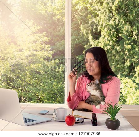 Mature woman wearing pink bathrobe holding her family cat while working from home in front of large window with bright daylight and trees in background. Haze light effect applied to image.