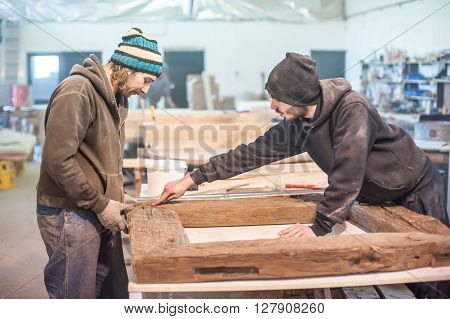 Carpenter work on wood plank in workshop