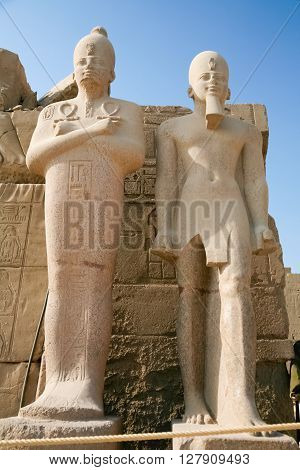 two statues sculptures of Egyptian pharaoh king in landmark Temple of Karnak monument declared a World Heritage by Unesco in Luxor Egypt Africa
