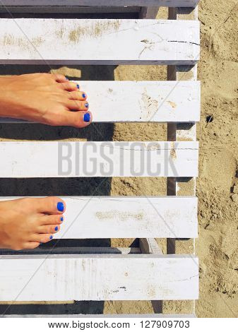 Woman's feet and white bench on the beach,  white sand beach