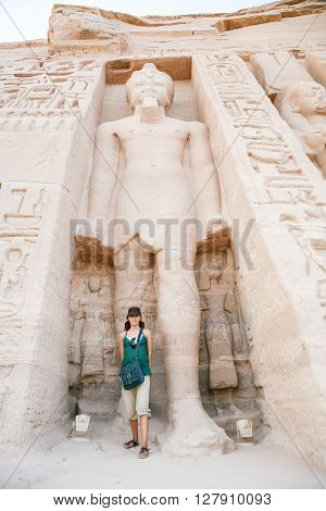 tourist woman standing down giant Ramses sculpture in facade of famous Egyptian temple of Nefertari and Hathor in Abu Simbel public monument from 13th century Before Christ in Nubia Egypt Africa