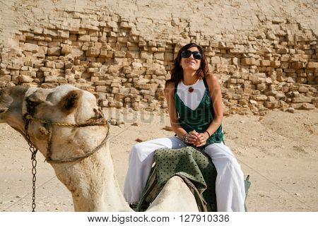 brunette tourist woman portrait sitting riding on white dromedary or arabic camel resting on desert next to Bent Pyramid in Dahshur Egypt Africa for Sneferu pharaoh ** Note: Soft Focus at 100%, best at smaller sizes